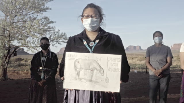 a young woman holding a drawing, with her family in the background, to help the navajo people understand the severity of covid19 - navajo culture stock videos & royalty-free footage