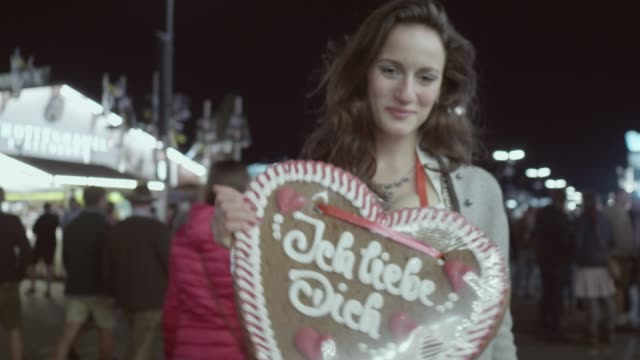 young woman holding a gingerbread heart at oktoberfest, saying i love you, ich liebe dich - liebe stock videos & royalty-free footage