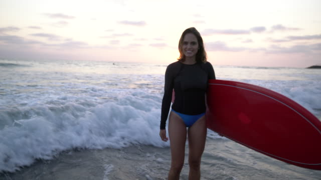 ws young woman holding a red surfboard on the beach - surfboard stock videos & royalty-free footage