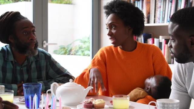 若い女性の赤ん坊を保持し、ディナー テーブルを囲んで家族と彼女の父親に話して