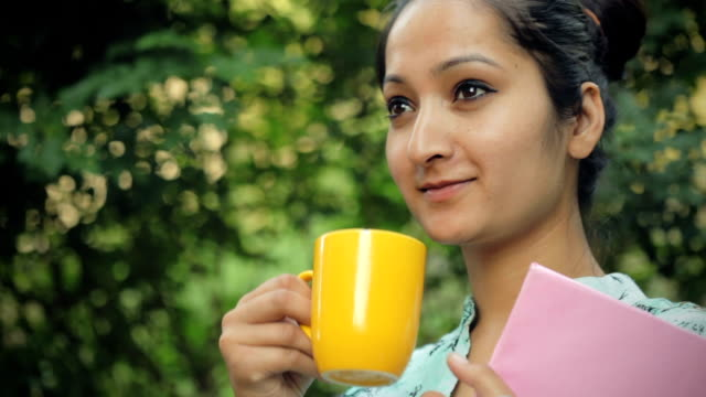 young woman holding book, enjoying coffee in fresh air. - black hair stock videos & royalty-free footage