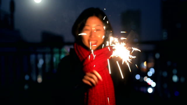 young woman holding burning sparklers at night - only mid adult women stock videos and b-roll footage