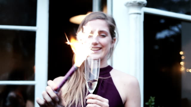 Young woman holding champagne flute and playing with cracker