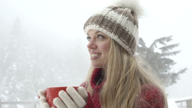 Young woman holding coffee cup and enjoying coffee during winter