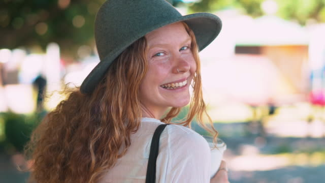 slo mo young woman holding coffee cup and looking at camera in a park - redhead stock videos & royalty-free footage