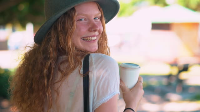 SLO MO Young woman holding coffee cup and looking at camera in a park