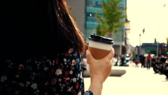 ung kvinna som håller kaffekoppen gå på gatan - slit och släng bildbanksvideor och videomaterial från bakom kulisserna