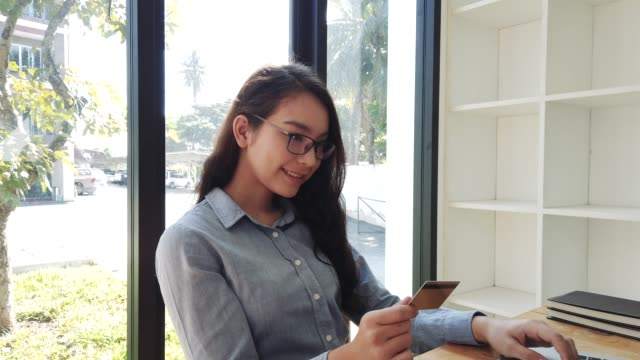 young woman holding credit card for making payment online shopping with laptop. home online shopping concept with credit card and laptop - spending money stock videos & royalty-free footage
