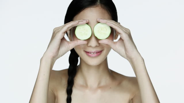young woman holding cucumber slices over eyes - cucumber stock videos & royalty-free footage