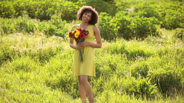Young woman holding flowers in field