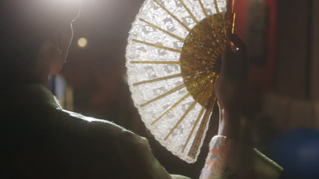 ms young woman holding folding fan / england, united kingdom - hand fan stock videos and b-roll footage