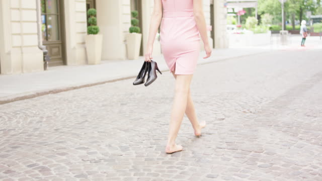 vídeos y material grabado en eventos de stock de joven mujer sosteniendo los tacones en la mano, sintiéndose aliviado. caminar por la ciudad - tacones altos