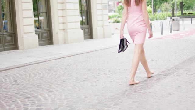 vidéos et rushes de jeune femme tenant dans la main les talons, se sentant soulagé. promenade dans la ville - femme fatale