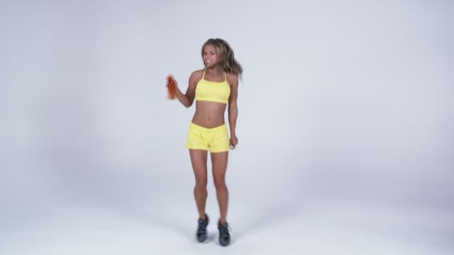 vídeos y material grabado en eventos de stock de ws young woman holding juice bottle and dancing / orem, utah, usa   - orem