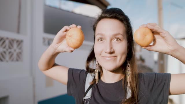 vídeos de stock e filmes b-roll de young woman holding mandarins in front of her eyes - village