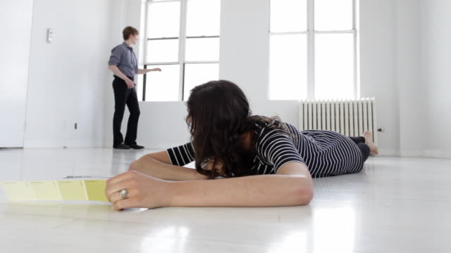 WS Young woman holding paint swatch lying on floor, young man standing by window in background in empty apartment