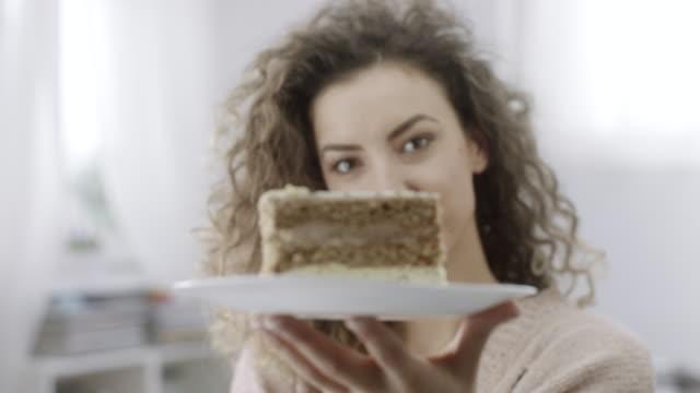 vídeos y material grabado en eventos de stock de mujer joven sosteniendo plato con rebanada de pastel en él - tentación