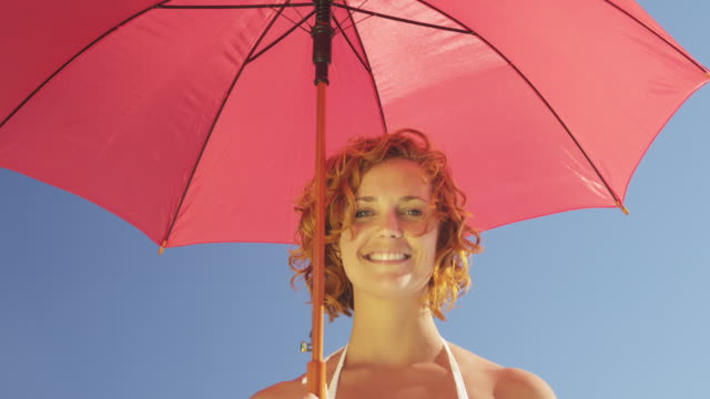 young woman holding red umbrella, looking to camera and smiling