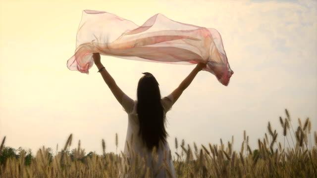 young woman holding scarf at sunset - 手足点の映像素材/bロール