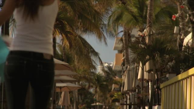 SLO MO MS Young woman holding shopping bags walking on sidewalk / South Beach, Florida, USA