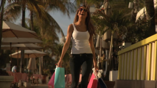 SLO MO MS Young woman holding shopping bags walking on sidewalk / South Beach, Florida, USA