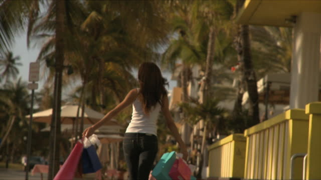 slo mo ms young woman holding shopping bags walking on sidewalk / south beach, florida, usa - tragetasche oder tragebeutel stock-videos und b-roll-filmmaterial