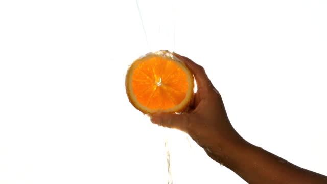 Jovem mulher Segurando a fatia de laranja com Sunburst água