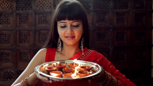 ms young woman holding  tray of small oil lamps and smiling / singapore - bangs stock videos & royalty-free footage
