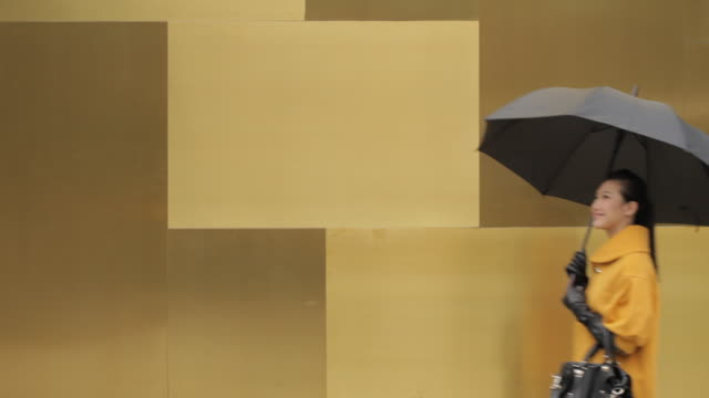 ms young woman holding umbrella walking past yellow wall/ china - umbrella stock videos and b-roll footage