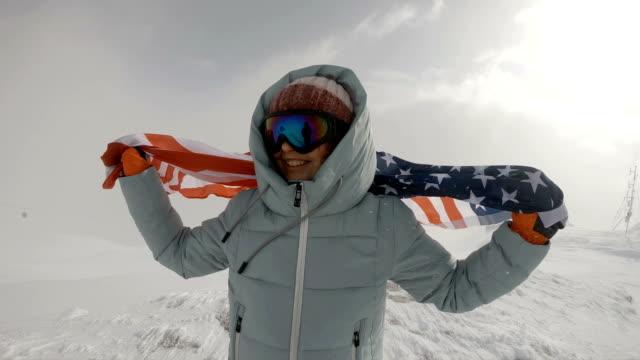 冬にアメリカの国旗を保持している若い女性 - ウィンターコート点の映像素材/bロール