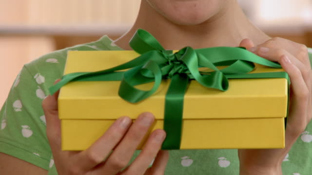 cu tu young woman holding wrapped gift and smiling / berlin, germany - birthday gift stock videos & royalty-free footage