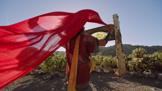 SLO MO. Young woman holds a flowing red scarf overhead that is carried away by the wind in desert ghost town.