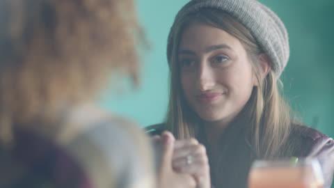 vídeos y material grabado en eventos de stock de ots. young woman holds hands with her partner and says i love you on date at local restaurant. - vinculación