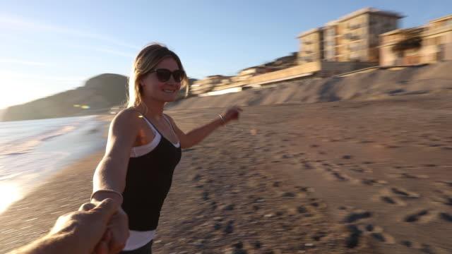 Young woman holds man's hand, runs along beach