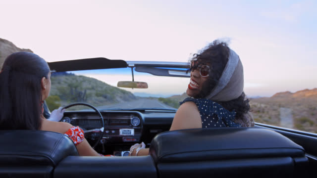 ms. young woman holds scarf in the air in classic convertible and laughs with friends on desert road trip. - land vehicle stock videos & royalty-free footage