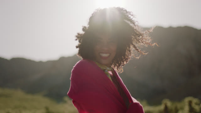 MED SLO MO. Young woman holds up flowing red scarf in the wind and wraps it around herself as she smiles at camera.