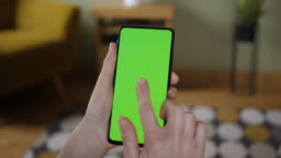 Young Woman Home Sitting on a Couch with Green Screen Smartphone in Vertical Mode. Girl Using Touch Screen Mobile Phone. Girl Using Smartphone, Browsing Internet, Watching Video Content, Blogs. POV.