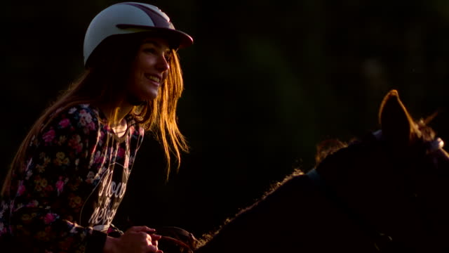 young woman horseback riding at sunset - horseback riding stock videos & royalty-free footage