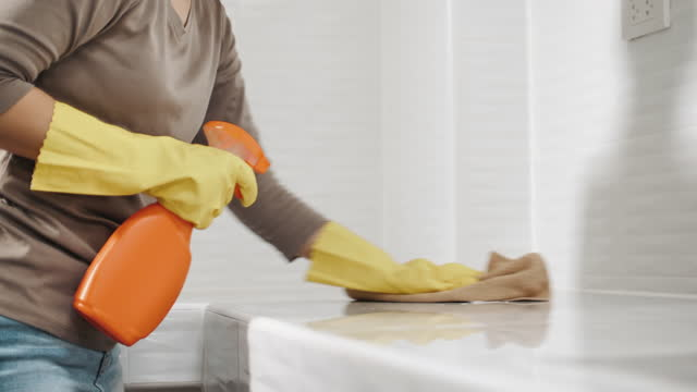 young woman housekeeper in apron is cleaning, wiping down table surface with yellow gloves - glove stock videos & royalty-free footage
