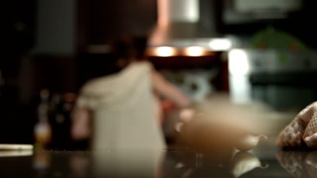vidéos et rushes de femme au foyer de jeune femme de cuisson dans la cuisine - plan large