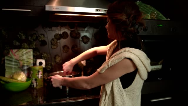 young woman housewife stirring a meal in a cooking pot on the hot plate in the kitchen - stereotypical housewife stock videos & royalty-free footage