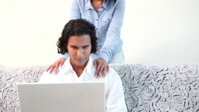 woman hugging her boyfriend that is using the laptop on the sofa - 中年カップル点の映像素材/bロール