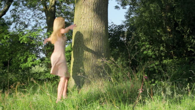 WS PAN Young woman hugging tree trunk in meadow / London, UK