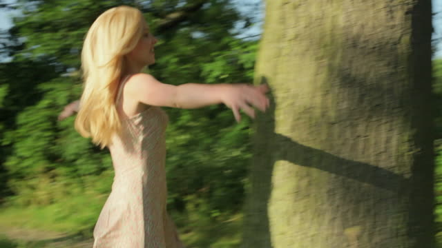 ms pan young woman hugging tree trunk in meadow / london, uk - hugging tree stock videos & royalty-free footage