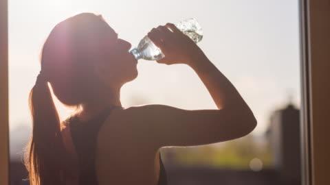ung kvinna hydrating efter högintensiv träning - dricksvatten bildbanksvideor och videomaterial från bakom kulisserna