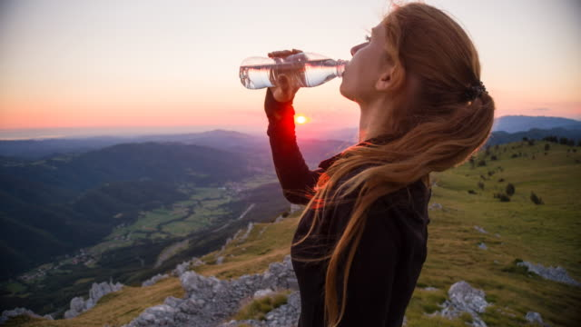 Young woman hydrating after reaching the top of a mountain
