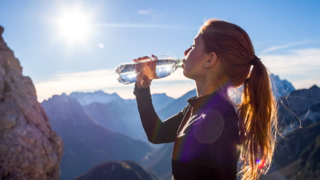Young woman hydrating after running to top of the mountain