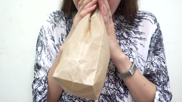 young woman hyperventilating and breathing in paper bag - anxiety stock videos & royalty-free footage