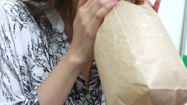young woman hyperventilating and breathing in paper bag - paper bag stock videos & royalty-free footage