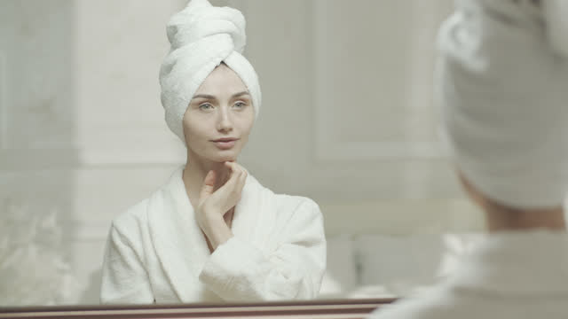 young woman in a bathrobe and a towel moisturizes her skin with a spray of water and looks at her reflection in the mirror. - bathrobe stock videos & royalty-free footage
